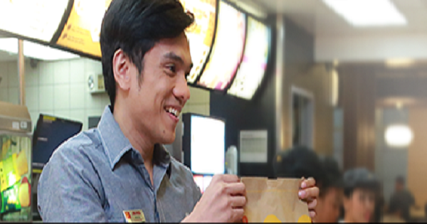 McDonald's manager trainee holding a paper bag
